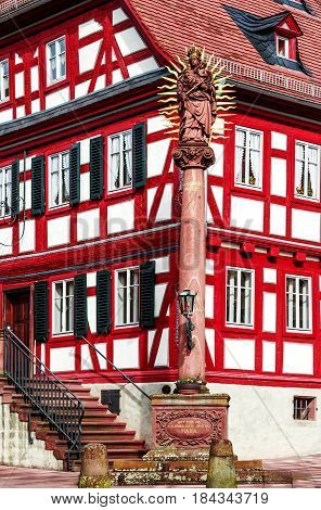 Historic half-timbered house with Holy Maria column on the market square in Amorbach, Germany