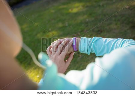 Female jogger checking her fitness band in the park