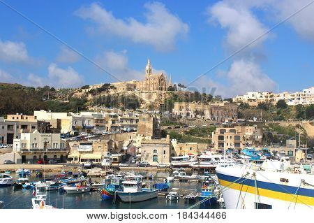 Mgarr, Gozo, Republic of Malta, with its port and the church on the hill