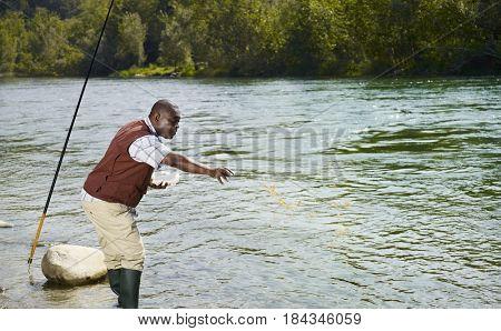 Black man throwing chum into stream
