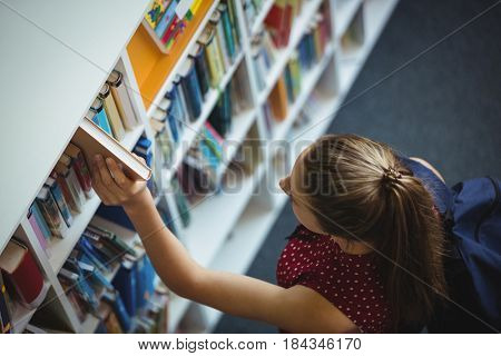 High angle view of schoolgirl selecting book from bookshelf in library at school