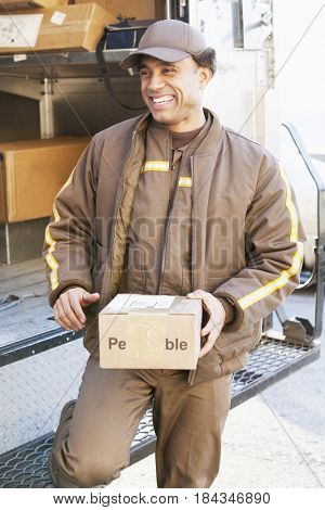 Smiling Hispanic delivery man holding cardboard box