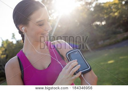 Smiling female jogger listening to music on mobile phone in the park