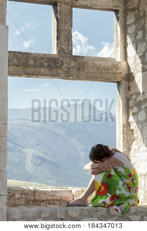 Back view of girl is putting her head on knees and looking at mountain window view