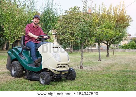 Gardener Cutting The Grass Of A Garden Seated On Lawn Mower