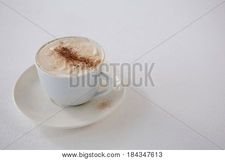 Close-up of coffee cup with creamy froth on white background