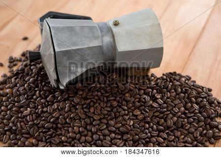 Coffee beans with metallic coffeemaker on wooden table