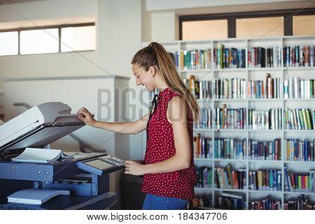 Happy schoolgirl using Xerox photocopier in library at school