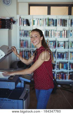 Portrait of happy schoolgirl using Xerox photocopier in library at school