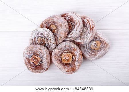 Dried flattened persimmon fruits on white background. Top view.