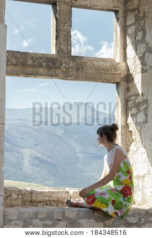 Back view of young woman in sundress is looking at view from window