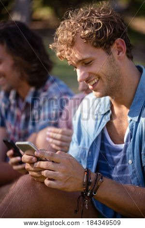 Man text messaging on mobile phone in park on a sunny day