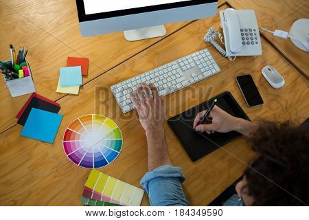Graphic designer using graphic tablet and desktop in creative office