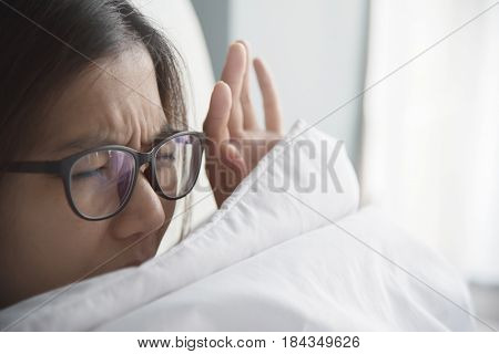 Asian woman having trouble about getting up early in the morning.