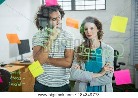 Thoughtful executives looking at sticky note in creative office