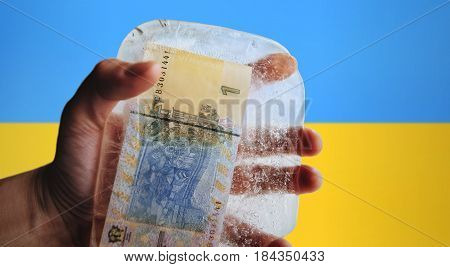 Ukrainian money in ice on a flag background. Devaluation, financial crisi.