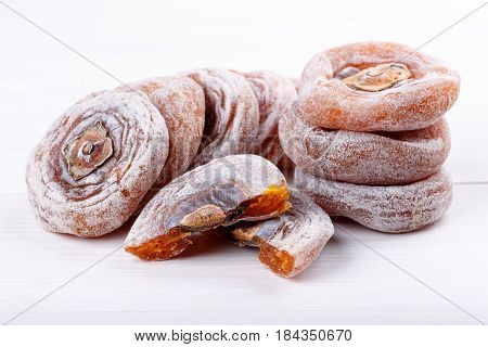 Dried flattened persimmon fruits on white background