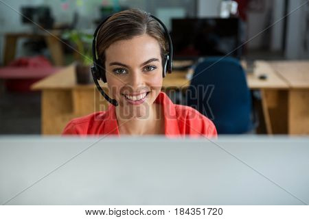 Portrait of smiling female executive with headphones at creative office
