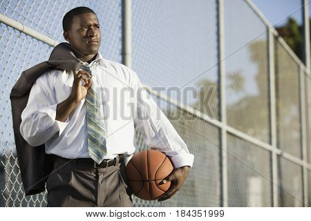 Black businessman holding basketball