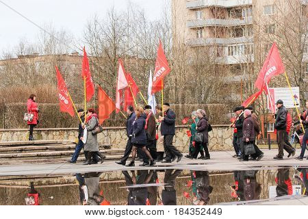 Kirishi, Russia - 1 May, Group of people with flags going to a rally,1 May, 2017. People at the May demonstration and rally in the Russian provincial government.
