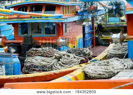 Close up view of winches and coiled ropes on colorful fishing boats moored next to each other