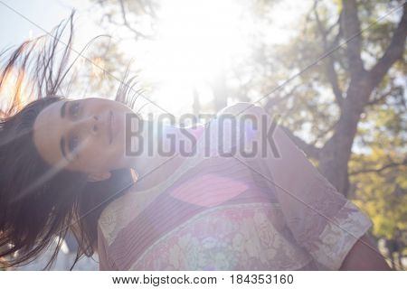 Woman swaying her hair in park on a sunny day