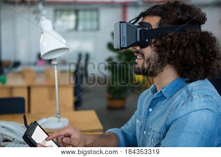 Graphic designer using the virtual reality headset and digital tablet in creative office