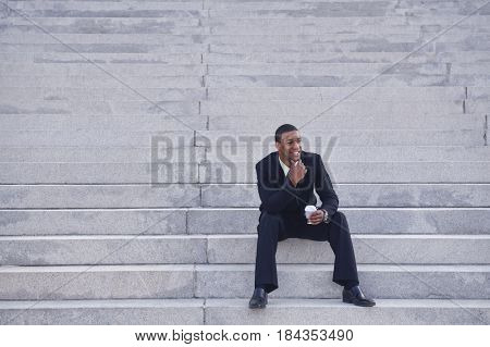 African American businessman drinking coffee on steps