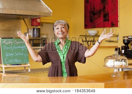African American business owner with arms outstretched in cafe