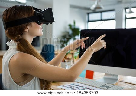Female graphic designer using the virtual reality headset in creative office