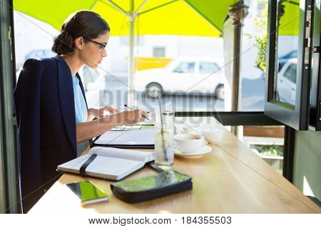 Focused female executive writing in diary at café