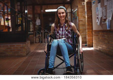 Portrait of smiling disabled schoolgirl on wheelchair in corridor at school