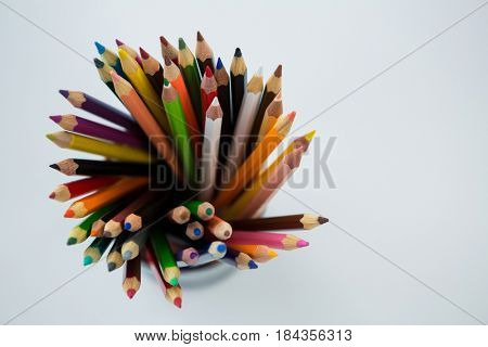 Colored pencils kept in pencil holder on white background
