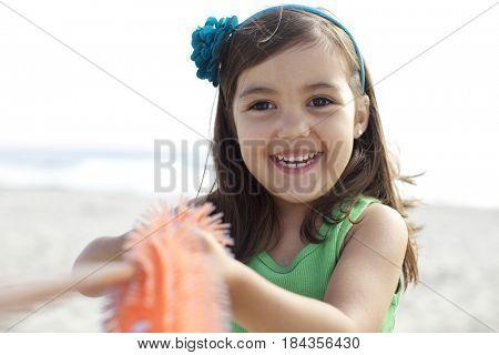 Grinning Hispanic girl on beach
