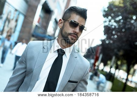 Successful dedicated young businessman walking on street in business district wearing suit tie and sunglasses.