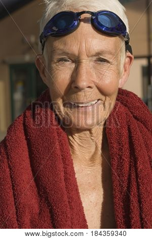 Caucasian woman in goggles wrapped in towel