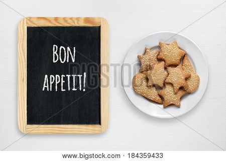Cookies in plate and small blackboard with Bon appetit wishes on white wooden table