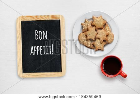 Cookies coffee cup and small blackboard with Bon appetit wishes on white table