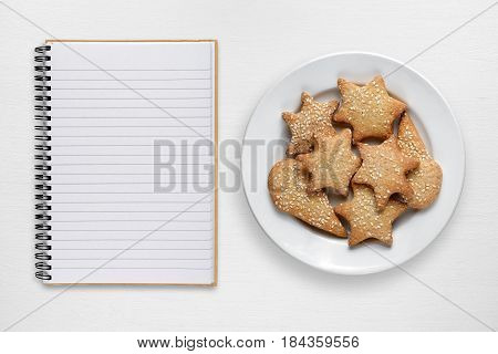 Blank recipe book and cookies on white table