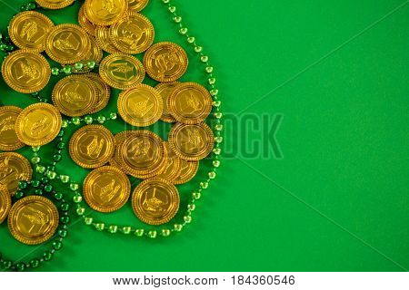 St Patricks Day gold chocolate coins and beads on green background