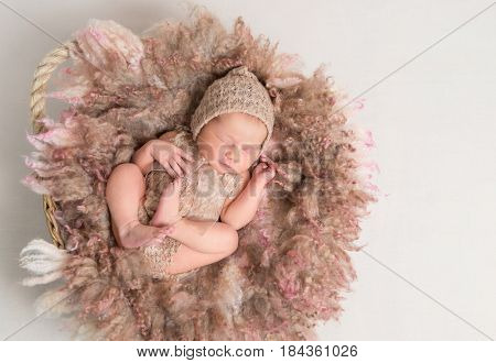 Sweet child sleeping on brown furry pillow, dressed in knitted brown suit with hat, topview
