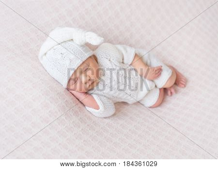 Sweet baby sleeping on his side, dressed in knitted white suit and a white hat