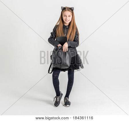 Fashionable teenage girl in a black jacket and with ears like a cat on his head