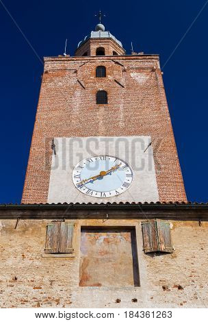 Castelfranco Veneto - February 2017, province of Treviso, comune of Veneto, Italy: View of Bell Tower with clock, windows with wooden shutters and medieval fresco