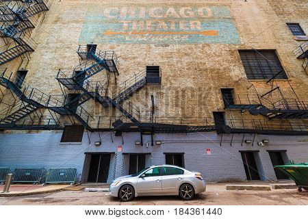 Chicago - March 2017, Illinois, USA: Wide angle view of Chicago Theater wall with fire stairs, doors, hand written graffiti sign with orange arrow on blue background, car parked on the street