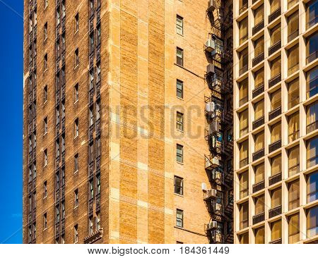 Block of flats in Chicago, apartment building in downtown against the blue sky, house made of brown bricks