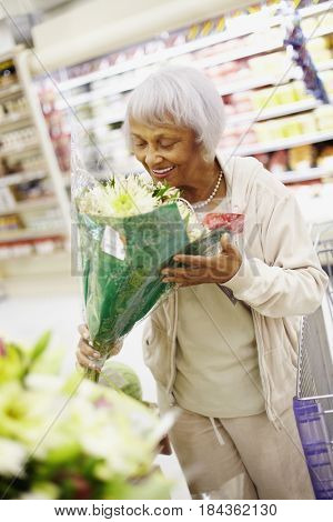 Senior African American woman in grocery store with bouquet of flowers