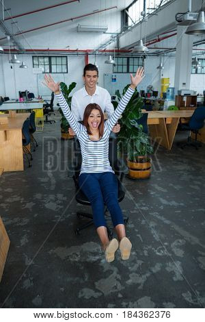 Man pushing woman on chair in creative office