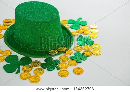 St. Patricks Day leprechaun hat, shamrocks and chocolate gold coins on white background