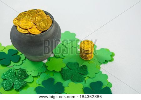 St. Patricks Day shamrock and pot filled with chocolate gold coins on white background